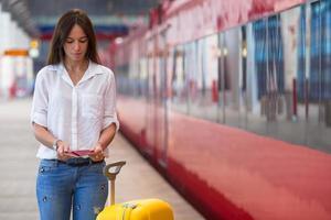 jovem caucasiana com bagagem na estação viajando de trem