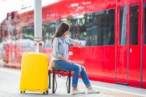 linda jovem com bagagem em uma estação de trem