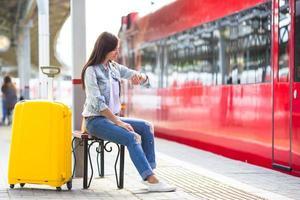 jovem com bagagem na plataforma esperando o aeroexpress foto
