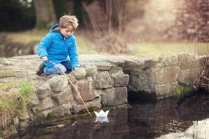 menino navegando em um barco de papel