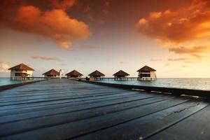 mulher em um vestido no pôr do sol maldivo