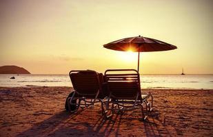 cadeiras de praia estilizadas vintage e guarda-chuva ao pôr do sol.