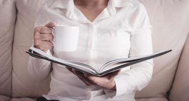 mulher sentada no sofá lendo um livro segurando uma xícara foto