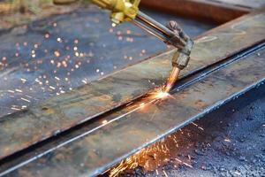 trabalhador cortando placa de metal foto