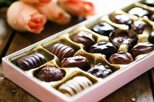 deliciosos bombons de chocolate com um buquê de rosas. foto