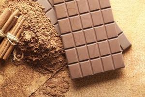 barras de chocolate, cacau e paus de canela foto