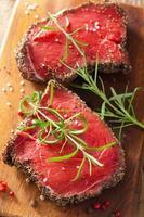 bife de carne crua com especiarias e alecrim em fundo de madeira foto