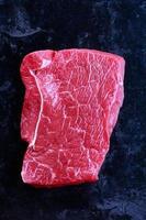 carne crua em um fundo preto foto