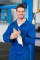 mecânico limpando as mãos com pano foto