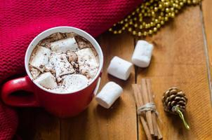 xícara de chocolate quente com canela e marshmallows foto