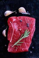 carne crua com especiarias em um fundo preto foto