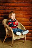 menino sentado na cadeira de vime foto