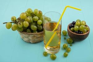 suco de uva uvas em fundo azul foto