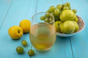 vista lateral de suco de uva e frutas em fundo azul foto