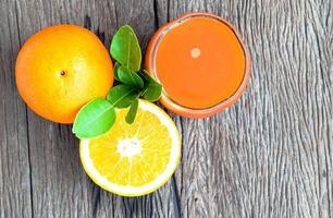 suco de laranja e laranjas no chão de madeira foto