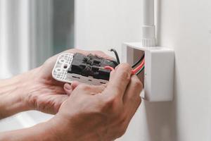 eletricista instala tomada elétrica foto