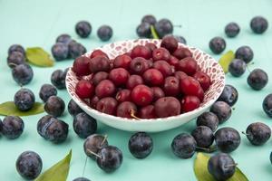 fotografia de alimentos postura plana de cerejas e frutas de abrunheiro foto