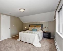 quarto perfeito com paredes cinzentas e roupa de cama branca. foto