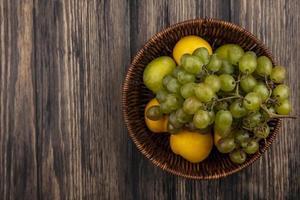 frutas sortidas em uma cesta no fundo de madeira foto