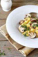 polenta com cogumelos e verduras no prato branco foto