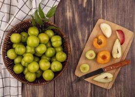 frutas frescas inteiras e fatiadas em fundo de madeira foto