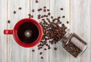xícara de café e grãos de café derramados no fundo de madeira foto
