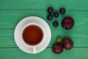 xícara de chá e frutas sobre fundo verde foto