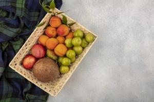 frutas sortidas em uma cesta em fundo neutro foto