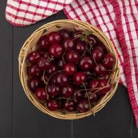 vista de cima de cerejas em uma cesta em tecido xadrez