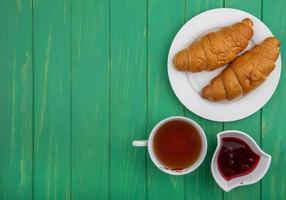 chá com frutas e torradas em fundo verde de madeira foto