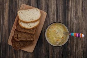 pão fatiado e sopa em fundo de madeira