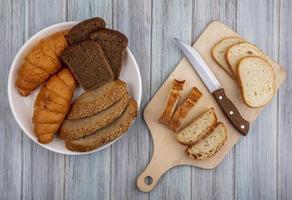Pão fatiado sortido em fundo de madeira