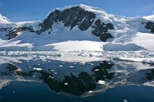 montanha coberta de neve com seu reflexo foto