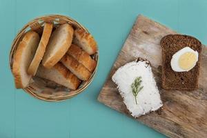 pão fatiado e queijo no fundo azul foto