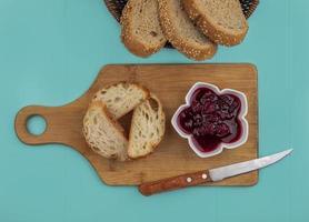 pão fatiado e frutas no fundo azul foto
