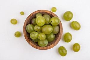 uvas brancas em uma tigela no fundo branco foto