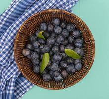 cesta de frutas escuras frescas em um fundo azul foto