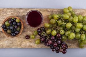 frutas e suco em uma placa de corte em fundo cinza foto
