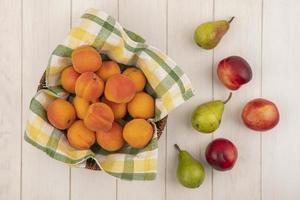 frutas frescas em uma cesta no fundo de madeira foto