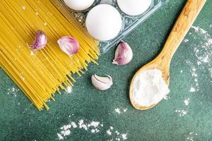 massa crua com farinha e ovos em um fundo verde