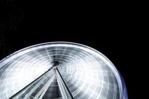 lapso de tempo de uma roda gigante iluminada foto