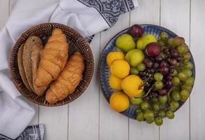 frutas e pão em pano em fundo de madeira