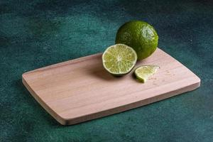 vista lateral de limão com uma fatia no tabuleiro
