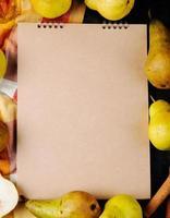 vista superior de um caderno de desenho e peras frescas maduras em fundo preto