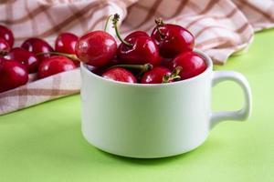 vista frontal de cerejas em uma xícara