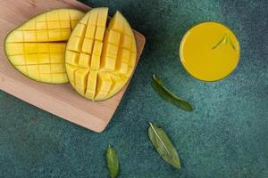 vista superior fatiada de manga em uma lousa com um copo de suco de laranja foto