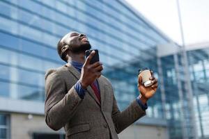 homem feliz segurando telefone e café