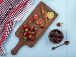 vista superior de morangos frescos em uma placa de cozinha de madeira foto