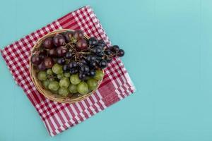 vista superior de uvas em tecido xadrez em fundo azul