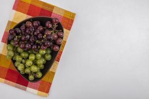 vista superior das uvas em um pano xadrez em fundo branco com espaço de cópia